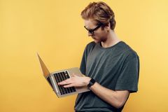 Jeune Guy Wearing Glasses Using Laptop attirant image libre de droits