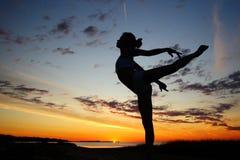 Jeune gymnaste féminin s'exerçant au lever de soleil Images stock