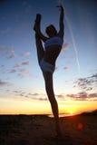 Jeune gymnaste féminin s'exerçant au lever de soleil Image stock