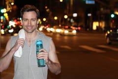 Jeune hanche et coureur moderne dans la ville avec la bouteille d'eau, buvant - image courante Photographie stock