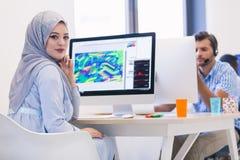 Jeune hijab de port arabe de femme d'affaires, fonctionnant dans son démarrage images libres de droits