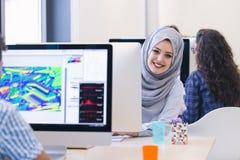 Jeune hijab de port arabe de femme d'affaires, fonctionnant dans son démarrage Photographie stock