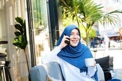 Jeune hijab de port de femme musulmane observ? par bleu photos stock