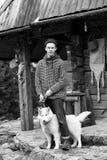 Jeune hippie avec le chien devant la maison en bois Image stock