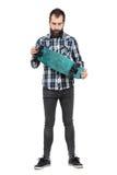 Jeune hippie dans la chemise de tartan tenant la planche à roulettes regardant vers le bas Images libres de droits