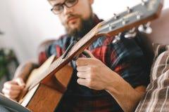 Jeune hippie de guitariste à la maison avec le capo de difficulté de guitare photographie stock