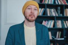 Jeune hippie infantile étonné attirant de perdant d'homme dans le chapeau jaune sur le fond bleu de bibliothèque de mur photo stock