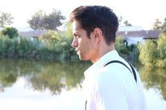 Jeune homme à côté d'un étang Image libre de droits