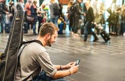 Jeune homme à l'aéroport international utilisant le téléphone intelligent mobile sur la porte terminale Images stock
