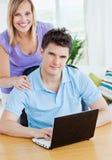 Jeune homme à l'aide d'un ordinateur portatif se reposant à une table Image stock