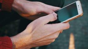Jeune homme à l'aide d'un smartphone sur un banc dans le parc de ville banque de vidéos