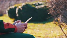 Jeune homme à l'aide d'un smartphone sur un banc dans le parc de ville clips vidéos