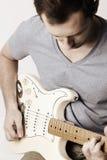 Jeune homme à l'aide d'une guitare électrique Photographie stock libre de droits