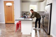 Jeune homme à l'aide de l'ordinateur portable dans la cuisine d'appartement Photographie stock libre de droits