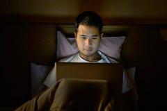 Jeune homme à l'aide de l'ordinateur portable dans son lit photographie stock libre de droits