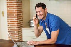 Jeune homme à l'aide de l'ordinateur portable et parlant au téléphone Image libre de droits