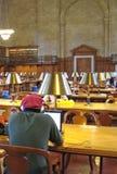 Jeune homme à l'aide de l'ordinateur portatif dans la bibliothèque Photographie stock libre de droits