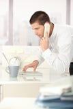 Jeune homme à l'aide de l'ordinateur portatif et du téléphone dans le bureau Image libre de droits