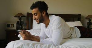 Jeune homme à l'aide de la tablette se trouvant le matin de sourire heureux de Guy Chatting Online In Bedroom d'hispanique de lit banque de vidéos