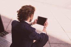 Jeune homme à l'aide de la tablette sur la rue Internet Images stock