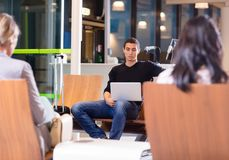 Jeune homme à l'aide de l'ordinateur portable au lobby de attente d'aéroport Image stock