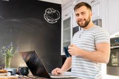 Jeune homme à l'aide de l'ordinateur portable au petit déjeuner photographie stock libre de droits