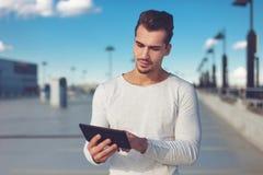 Jeune homme à l'aide du comprimé numérique extérieur, le grand espace Images stock