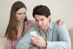 Jeune homme à l'aide du smartphone, ayant des problèmes, amie soucieuse Photo stock