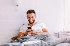 Jeune homme à l'aide du smartphone dans le lit Photographie stock libre de droits