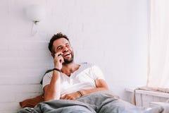 Jeune homme à l'aide du smartphone dans le lit Images libres de droits