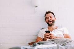 Jeune homme à l'aide du smartphone dans le lit Photos libres de droits
