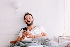 Jeune homme à l'aide du smartphone dans le lit Images stock