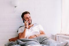 Jeune homme à l'aide du smartphone dans le lit Image libre de droits