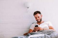 Jeune homme à l'aide du smartphone dans le lit Image stock