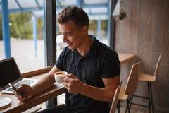 Jeune homme à l'aide du téléphone portable et buvant du café en café image stock