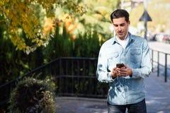 Jeune homme à l'arrière-plan urbain écoutant la musique avec des écouteurs Image libre de droits