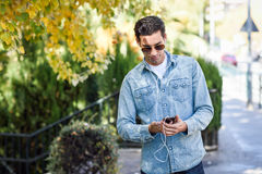 Jeune homme à l'arrière-plan urbain écoutant la musique avec des écouteurs Photo libre de droits