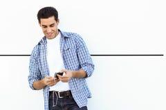 Jeune homme à l'arrière-plan urbain écoutant la musique avec des écouteurs Images stock