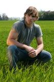 Jeune homme à l'herbe verte Image stock