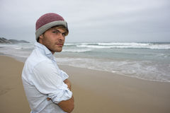 Jeune homme à l'océan le jour nuageux Image stock