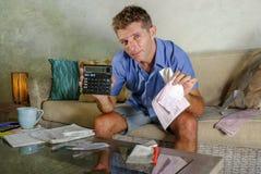 Jeune homme à la maison inquiété et soumis à une contrainte attirant calculant des dépenses d'impôts de mois avec des paiements d Photographie stock