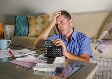 Jeune homme à la maison inquiété et soumis à une contrainte attirant calculant des dépenses d'impôts de mois avec des paiements d Photographie stock libre de droits