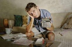 Jeune homme à la maison inquiété et soumis à une contrainte attirant calculant des dépenses d'impôts de mois avec des paiements d Image libre de droits