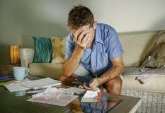Jeune homme à la maison inquiété et soumis à une contrainte attirant calculant des dépenses d'impôts de mois avec des paiements d Photo stock