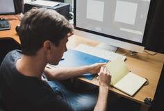 Jeune homme à la maison utilisant un ordinateur photographie stock