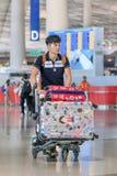 Jeune homme à la mode avec le chariot à bagage à l'aéroport capital de Pékin Internationa Photographie stock libre de droits
