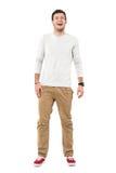 Jeune homme à la mode décontracté dans le pantalon beige et des espadrilles rouges riant la recherche Image stock