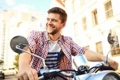 Jeune homme à la mode montant un scooter de vintage dans la rue Image stock