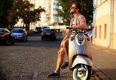 Jeune homme à la mode montant un scooter de vintage dans la rue Image libre de droits