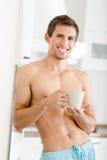 Jeune homme à moitié nu avec la tasse de thé à la cuisine Image libre de droits